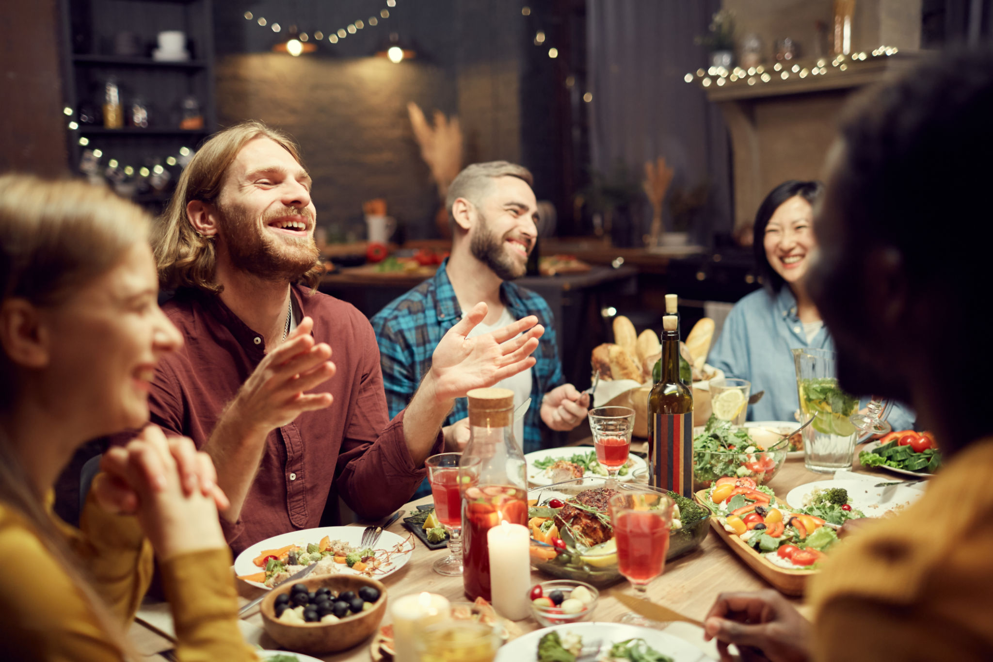 people laughing at dinner party table